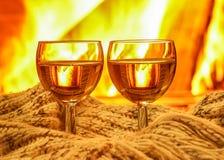 白葡萄酒和羊毛事两块玻璃临近舒适壁炉, 免版税图库摄影