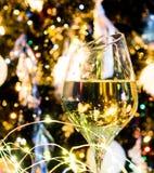 白葡萄酒或香槟在圣诞树前面与黄灯 免版税库存图片