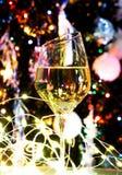 白葡萄酒或香槟在圣诞树前面与黄灯 图库摄影