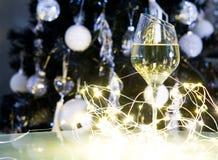 白葡萄酒或香槟在圣诞树前面与黄灯 库存图片