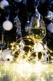 白葡萄酒或香槟在圣诞树前面与黄灯 免版税库存照片