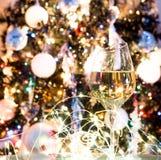 白葡萄酒或香槟在圣诞树前面与黄灯 库存照片