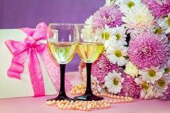 白葡萄酒或香槟在玻璃、当前箱子和花 库存图片