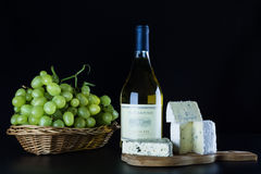 白葡萄酒瓶、青纹干酪和一束在黑背景的成熟葡萄 免版税库存照片