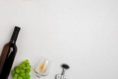 白葡萄酒瓶、玻璃和拔塞螺旋在白色背景 与拷贝空间的顶视图 图库摄影