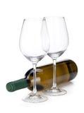 白葡萄酒瓶和二块空的玻璃 免版税库存图片