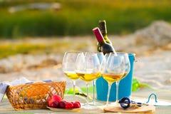 白葡萄酒的杯在海滩的在日落,野餐题材, 免版税库存照片