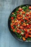 白薯、红萝卜、西红柿和狂放的火箭沙拉用希腊白软干酪在黑色的盘子服务 免版税库存照片