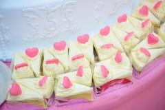 白蛋糕许多片断和由在自助餐线的桃红色巧克力心脏形状装饰 甜点和点心面包店 免版税库存图片