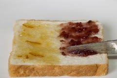 白面包用半橙皮马末兰果酱和草莓酱 免版税库存照片