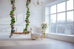 白革葡萄酒样式椅子在有大窗口和春天的古典内部室开花 免版税库存图片