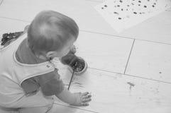 黑白,孩子倾倒在地板之上的水 库存图片