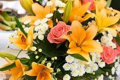 百合和玫瑰美丽的新娘花束在婚礼聚会 免版税库存照片