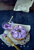 百吉卷用在土气桌上的蓝莓乳脂干酪与音乐纸张垂直布局 免版税库存照片