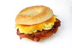 百吉卷用scrambledd鸡蛋、烟肉和切达干酪 库存图片