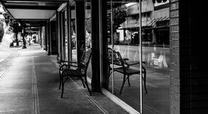 百货大楼在B&W的边路长凳 免版税库存照片