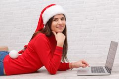 的一个女孩新年的欢乐衣裳在膝上型计算机后坐 免版税库存照片