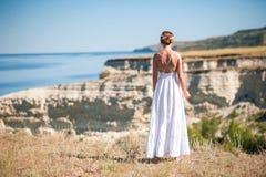 的一个女孩白色sarafan立场和为岩石和水照相的美好的本质 峭壁,土坎,峡谷 避难所,休息 免版税库存图片