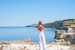 的一个女孩白色sarafan立场和为岩石和水照相的美好的本质 峭壁,土坎,峡谷 避难所,休息 免版税图库摄影