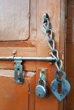 的一个棕色木门葡萄酒门闩、金属锁和一条老门链,异常的内部元素 库存图片