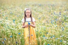 的一个美丽的女孩在一个开花的草甸的黄色sarafan步行 免版税库存照片