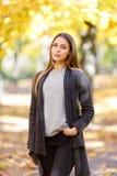 的一个美丽的女孩在秋天公园被弄脏的背景的黑浣熊  免版税库存照片