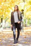 的一个美丽的女孩在秋天公园被弄脏的背景的黑浣熊  图库摄影