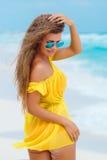 的一名妇女在一个热带海滩的黄色sundress 库存照片