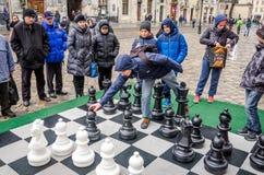 的一杆巨大的棋枰在露天使用与白色和黑片断的比赛孩子的争斗在街道上 免版税库存图片