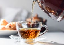的一杯茶倒从水壶的茶的 免版税库存图片