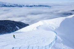 他的下降的挡雪板在足迹在山滑雪胜地和森林覆盖后边 库存照片