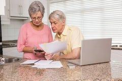 付他们的与膝上型计算机的资深夫妇帐单 免版税库存照片