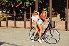 的两个时髦的年轻和性感的女孩自行车在夏天 免版税库存图片