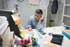 他的书桌的沮丧的办公室工作者 免版税库存照片