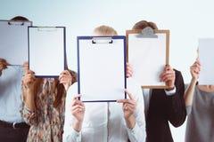 的买卖人队对负文件夹临近在白色背景的面孔 买卖人 免版税库存图片