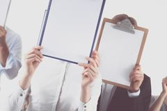 的买卖人队对负文件夹临近在白色背景的面孔 免版税库存照片