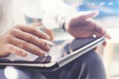 的人在手边拿着数字式片剂和使用电子笔的特写镜头观点,当工作在办公室时 指向片剂 免版税库存图片