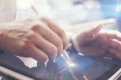 的人在手边拿着数字式片剂和使用电子笔的特写镜头观点,当工作在晴朗的办公室时 指向 免版税库存照片
