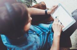的人在手边拿着数字式片剂和使用,当坐在扶手椅子的特写镜头观点在coworking的地方时 现有量指向 库存图片