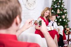 的人拍他的妻子和儿子的照片后面观点有圣诞节的 免版税库存图片