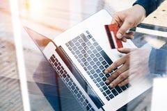 的人拿着信用卡的特写镜头观点手中和键入的膝上型计算机键盘,当坐在木桌上时 反映 库存照片