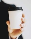 的人拿着白皮书咖啡杯的特写镜头观点拿走 嘲笑纸盒咖啡杯为去外面 垂直 免版税库存照片