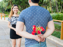 年轻从他的人掩藏的玫瑰后面和给他们他的女朋友 免版税库存照片