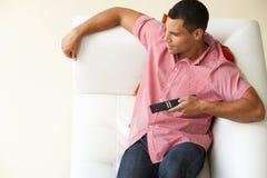 的人放松在沙发观看的电视上的顶上的观点 图库摄影
