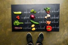 的人站立在新鲜蔬菜和卡路里附近的部份观点桌 图库摄影