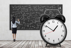 的企业夫人背面图在黑黑板写着算术惯例 巨大的闹钟在前景 一浓缩 免版税库存图片