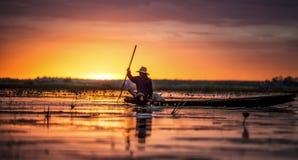 他的传统小船的渔夫在日出 免版税库存照片