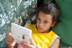 他的使用与电子游戏的业余时间的孩子 库存照片