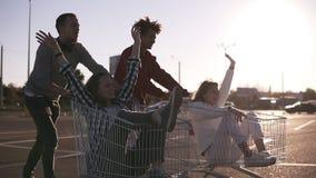的侧视图年轻朋友的获得乐趣户外在购物台车 赛跑在手推车的不同种族的年轻人 股票视频