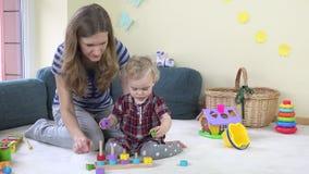 仔细的保姆妇女教小孩女孩拉扯在杆的木五颜六色的砖 股票视频